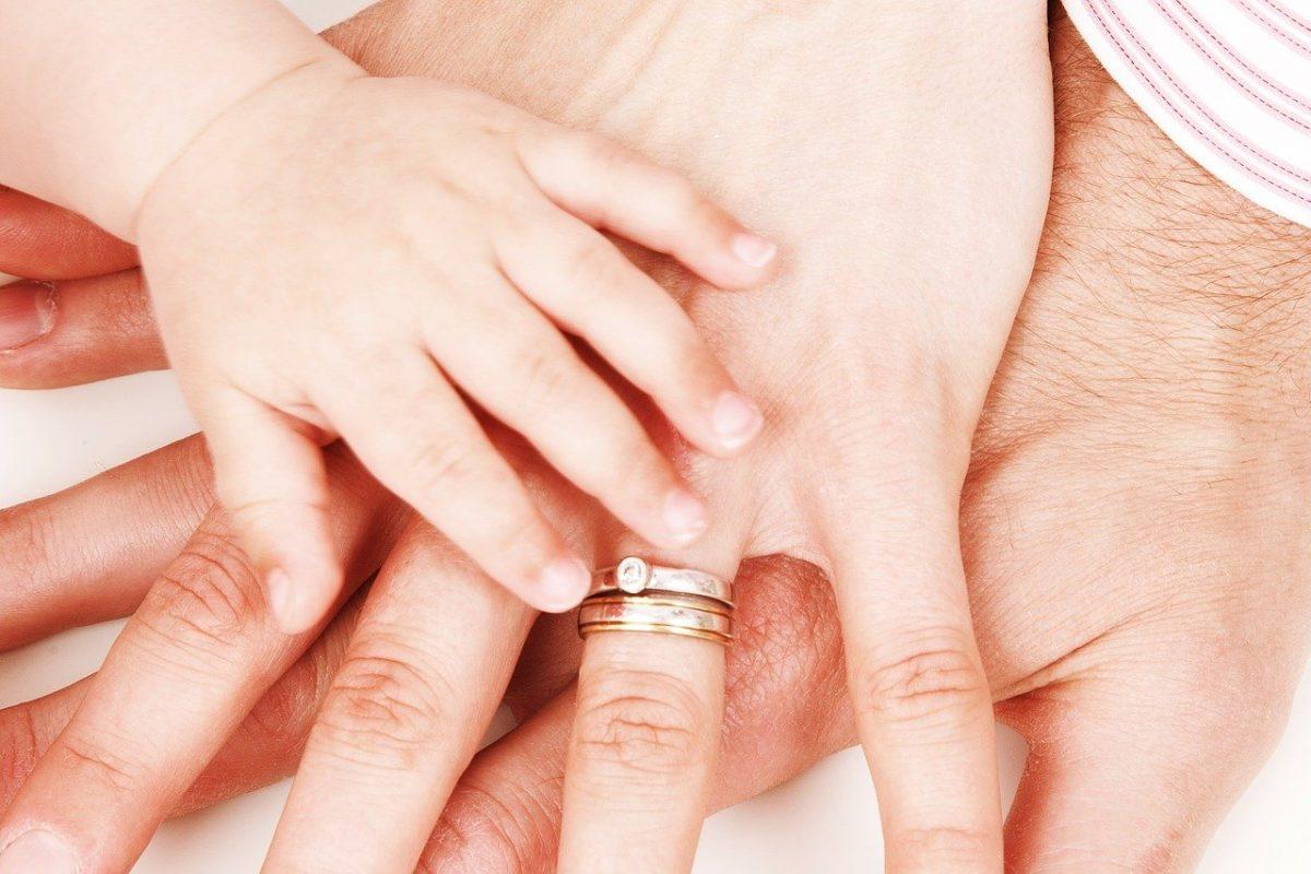 Drei Hände unterschiedlicher Generationen liegen übereinander und stellen Zusammenhalt dar