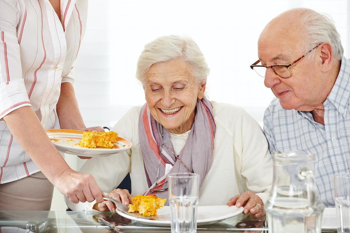 2 Senioren sitzen am Tisch und erhalten eine Mahlzeit serviert