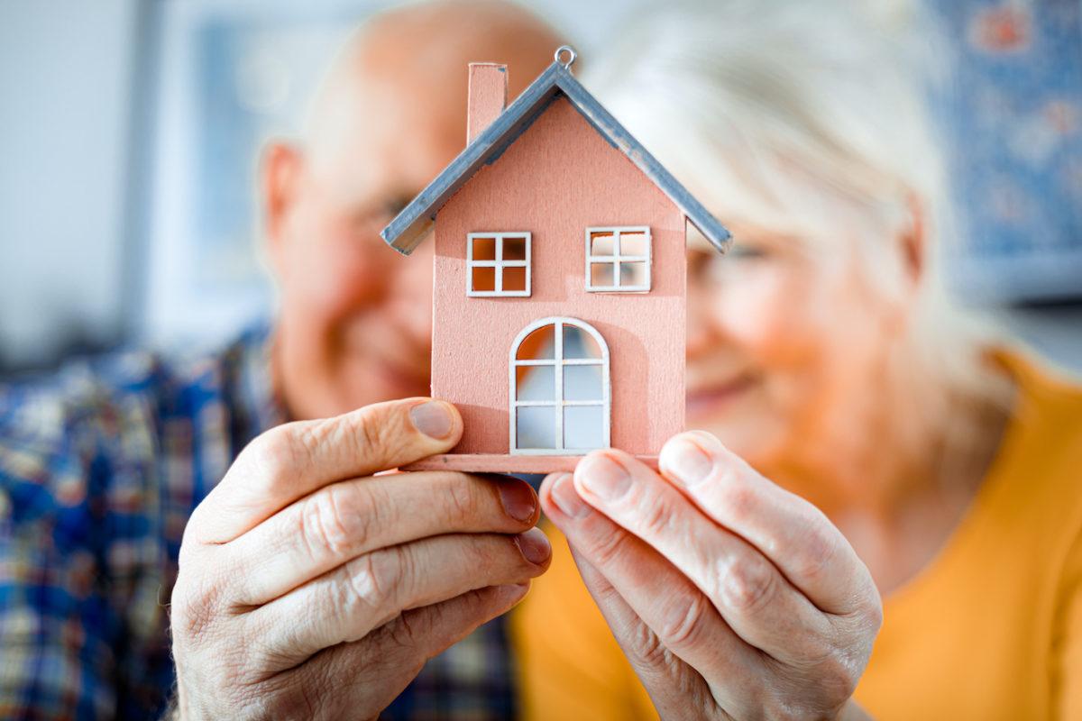 2 Senioren halten ein kleines Hausmodell in den Händen